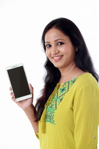 88978743 – young woman holding mobile phone against white background